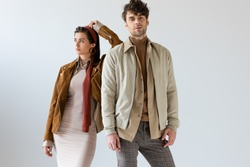 Attractive woman looking away and leaning on handsome man in autumn outfit on grey