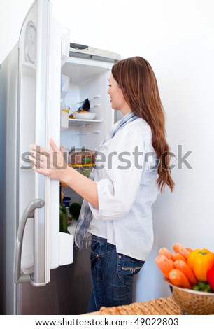 Attractive woman looking for something in the fridge at home