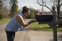 Attractive woman looks inside a mailbox.