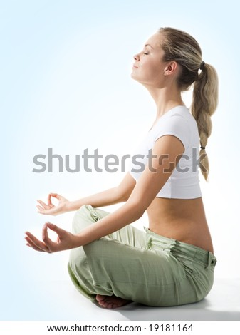 Attractive woman meditating in pose of lotus on blue background - stock photo