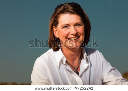 Attractive woman middle aged enjoying outdoors. Clear sunny spring day with blue sky.