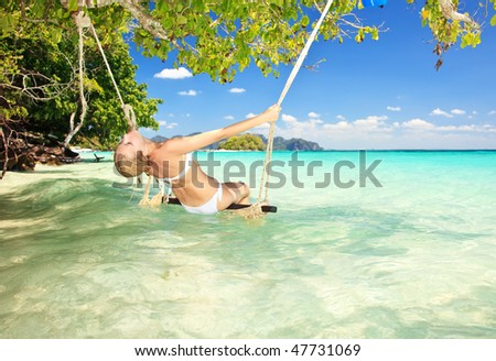 attractive woman on a swing in paradise