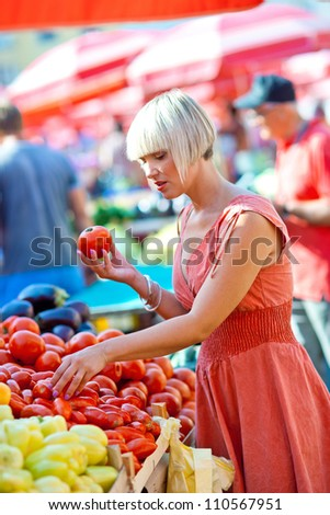 attractive woman on market choosing vegetables