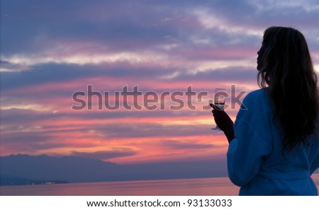 Attractive woman on the beach looking at colorful mythical beautiful sunset. Crete. Greece - stock photo