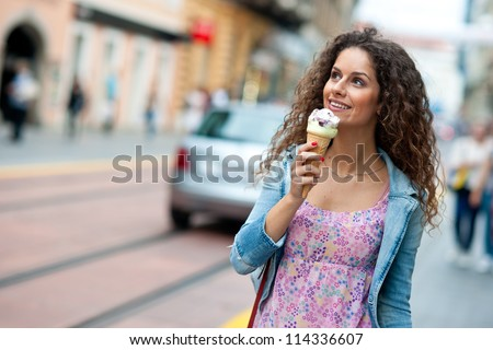 attractive woman on the street having fun and eating ice cream