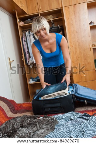 attractive woman packing clothes in luggage in her bedroom