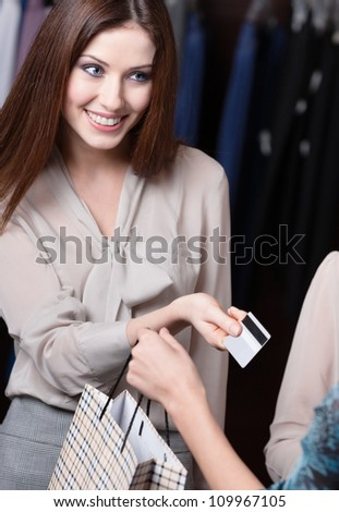 Attractive woman pays with credit card at the store