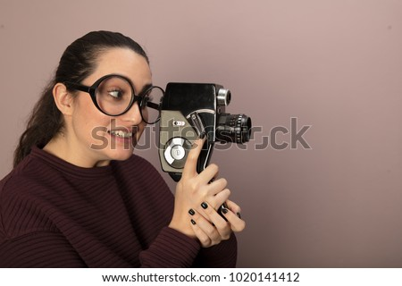 Attractive woman photographer wearing nerdy glasses peering into the viewfinder of a vintage video camera pointed towards blank copy space on a brown background