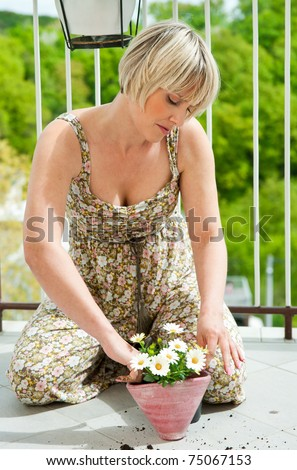 attractive woman planting flowers on home balcony