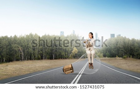 Attractive woman playing trumpet brass on asphalt road. Young businesslady in white business suit and gloves sitting on big light bulb with music instrument. Musician practicing and performing outdoor #1527431075