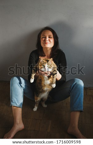 Attractive woman playing with funny red cat at home in the sunlight.
