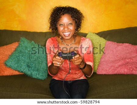Attractive woman plays video game with hand held controller