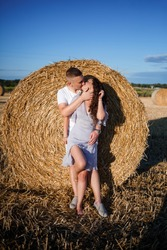 Attractive woman posing in the mown wheat fields with a sheaf in the village. Hay bales on the field after harvest, a place for a photo session of a beautiful Slavic couple