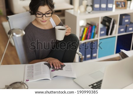 Attractive woman reading magazine at home