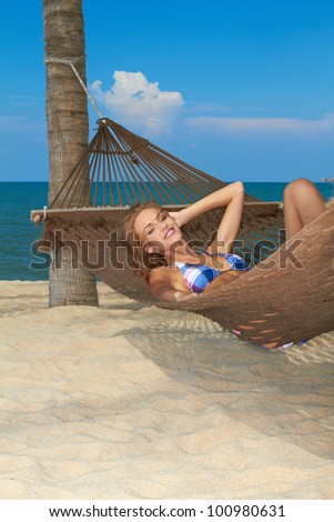 Attractive woman reclining in a hammock strung from a palm enjoying the tranquillity of a tropical beach