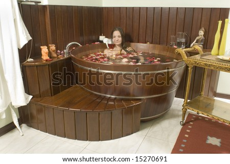 Attractive woman relaxing in a hot tub with a glass of wine while surrounded by flower petals. Horizontally framed shot.