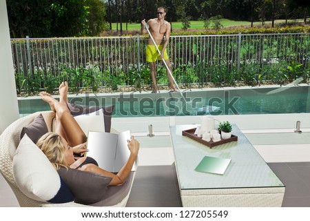Attractive woman relaxing in backyard patio with pool boy cleaning the pool