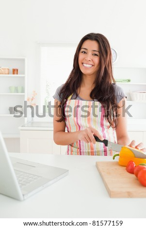 Attractive woman relaxing with her laptop while cooking vegetables in the kitchen