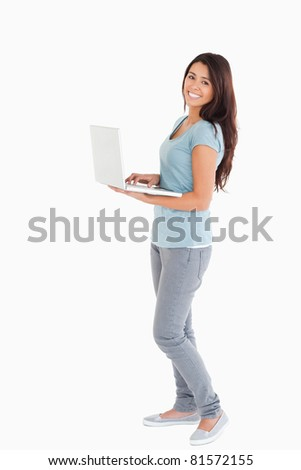 Attractive woman relaxing with her laptop while standing against a white background