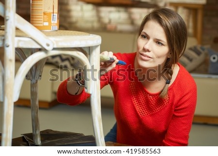 Attractive woman renewing, painting chair at home.
