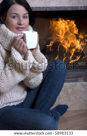 Attractive woman rests at fireplace