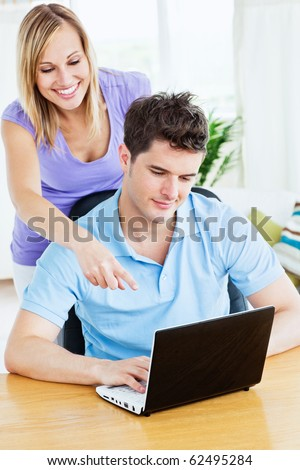 Attractive woman showing something on the computer to his boyfriend  standing in the living-room - stock photo
