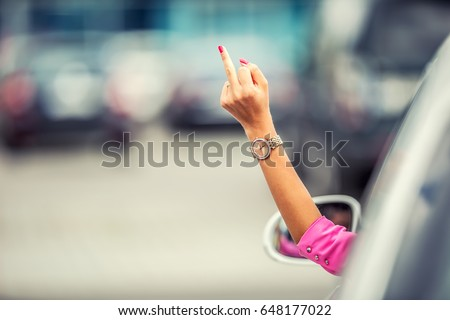 Attractive woman shows obscene gesture from a car.