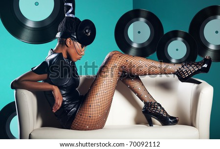 Attractive woman siting in white chair on records background