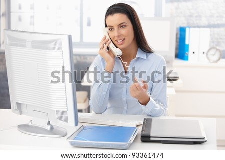 Attractive woman sitting at desk at work on landline phone call, gesturing, smiling.?