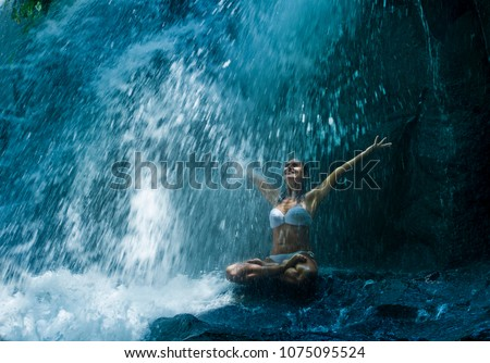 attractive woman sitting at rock in yoga pose for spiritual relaxation serenity and meditation at stunning beautiful waterfall and rain forest in Bali Summer holidays feeling free and peaceful