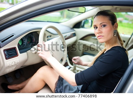 attractive woman sitting in driver seat in the car