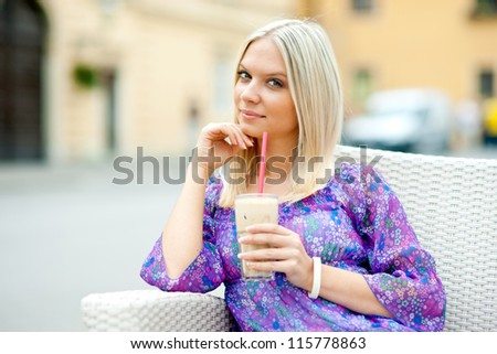 attractive woman sitting in outdoor cafe and drinking ice coffee