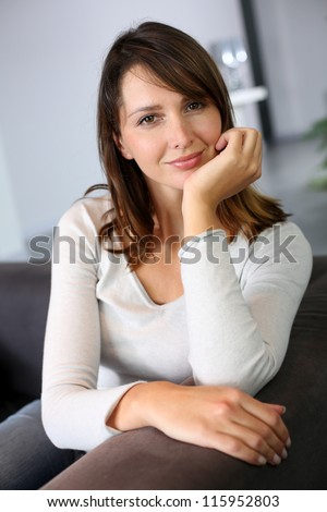 Attractive woman sitting in sofa at home
