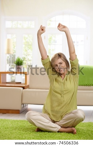 Attractive woman sitting on living room floor stretching with small smile.? - stock photo