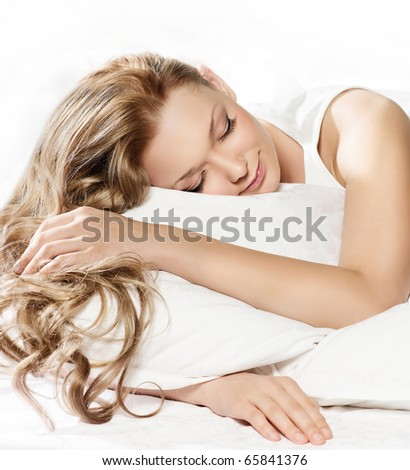 attractive  woman slipping in bed on white background