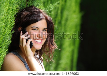 Attractive woman smiling on the phone in a park with a green unfocused background