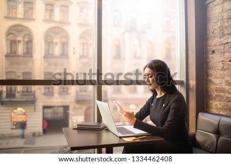 Attractive woman successful commercial real estate analyst checks the status of the account on smartphone while sitting with laptop computer in coffee shop near window with copy space. Online banking