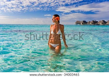attractive woman sunbathing in tropical resort waters near resort bungalows