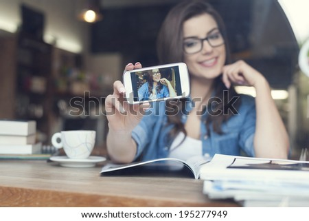 Attractive woman taking self portrait by mobile phone