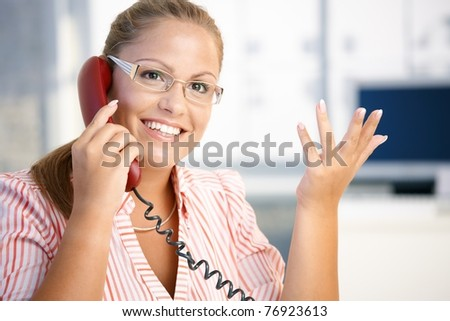 Attractive woman talking on phone in office, gesturing, smiling.?
