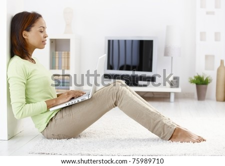 Attractive woman using laptop computer, sitting on floor of living room, smiling.?