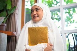 attractive woman wear hijab read quran. female muslim praying