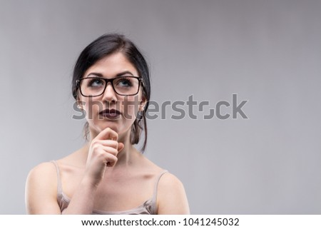 Attractive woman wearing glasses deep in thought looking up with a serious pensive expression and her hand to her chin over a grey background with copy space