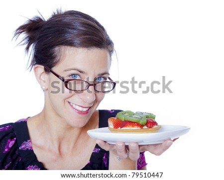 Attractive woman with a fruit tart in studio - stock photo