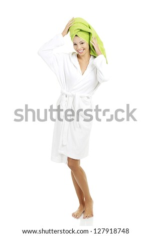 Attractive woman with a green towel on her head and bathrobe, isolated on white