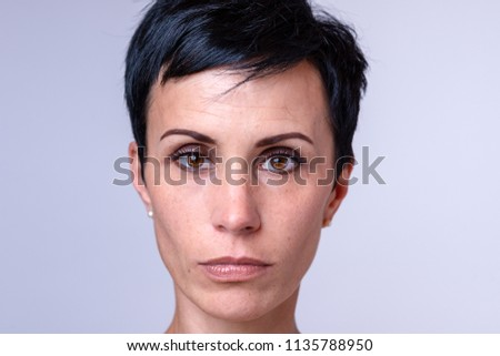 Attractive woman with a short modern hairstyle and big brown eyes looking solemnly at the camera, head shot over grey