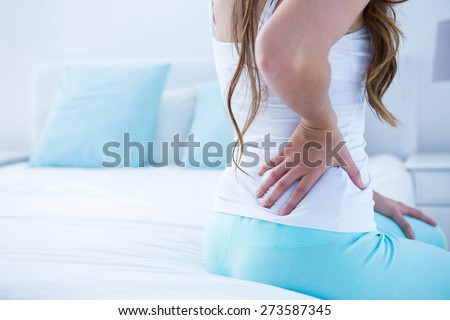 Attractive woman with back pain at home in the bedroom