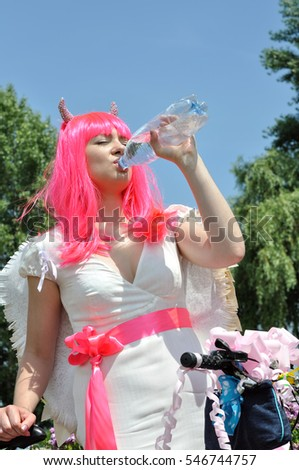 attractive woman with bike in demon costume drinks cold water in hot day