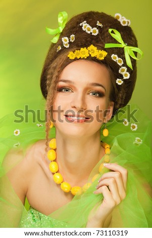 attractive woman with bows wild flowers in her hair and dress, with professional hairstyle and make up