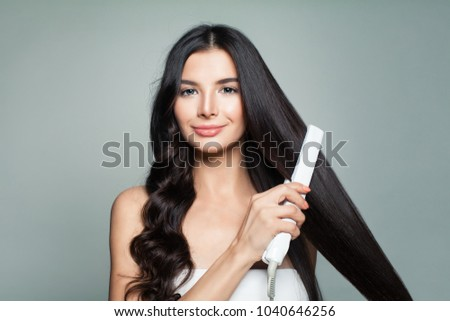 Attractive Woman with Curly Hair and Long Straight Hair Using Hair Straightener. Cute Smiling Girl Straightening Healthy Brunette Hair with Flat Iron.